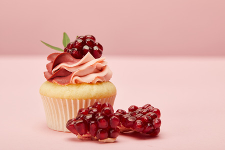Sweet cupcake with cream and garnet on pink surface