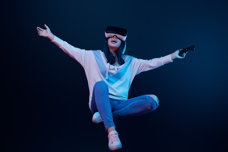 Happy woman in virtual reality headset levitating and holding joystick on blue background Foto de archivo