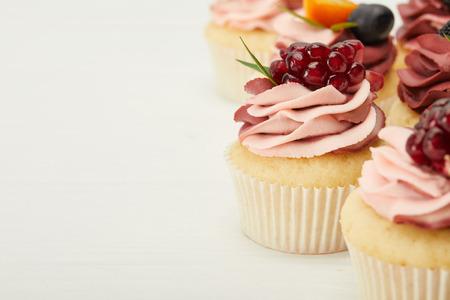 selective focus of cupcakes with cream and berries on white surface
