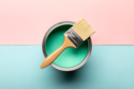 Top view of can on green paint and brush on pink and blue surface Standard-Bild - 122292210
