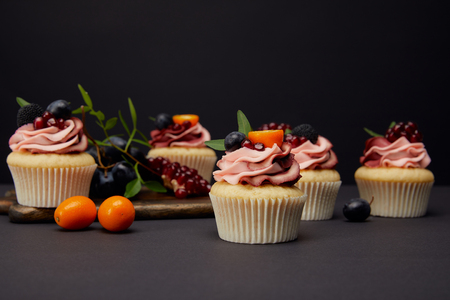 sweet cupcakes with berries and fruits on grey surface isolated on black