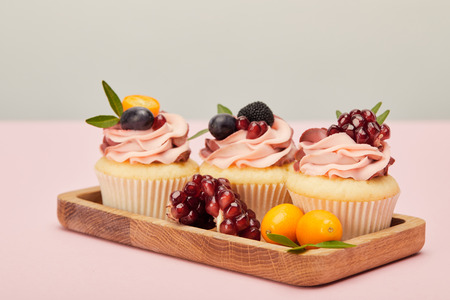 Wooden tray with sweet cupcakes on pink surface isolated on grey background