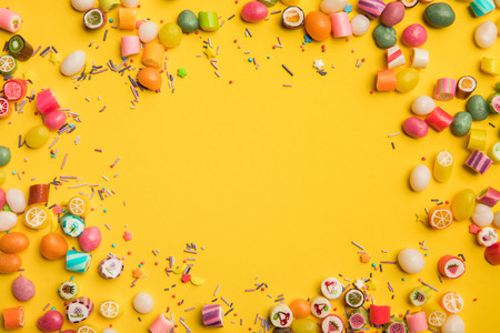 Frame of multicolored candies and sprinkles scattered on yellow background with copy space