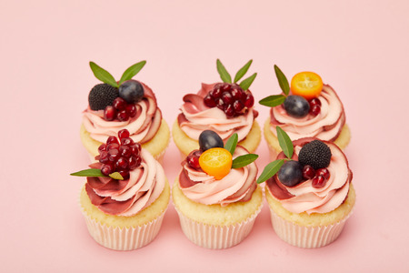 sweet cupcakes with fruits and berries on pink surface