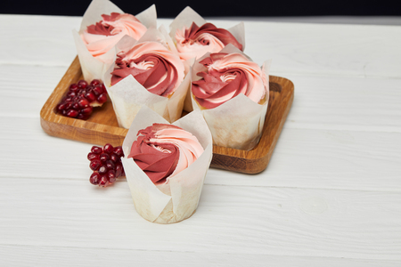 Cupcakes with cream and garnet on cutting board on white surface 版權商用圖片