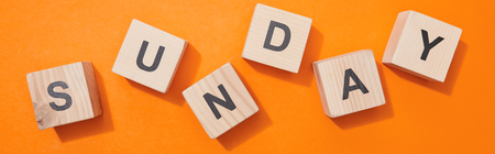 Panoramic shot of wooden cubes with letters on orange surface Stock Photo