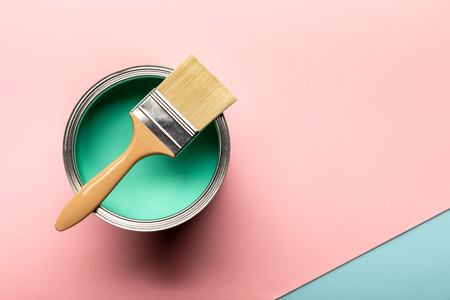 Top view of tin of green paint and brush on pink surface Banque d'images - 122292319
