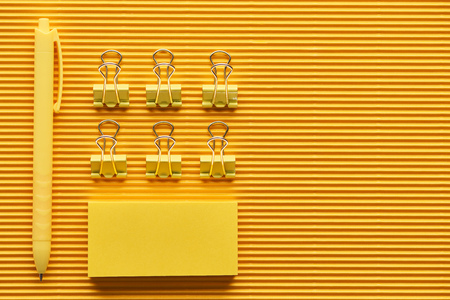 Top view of pen, paper clips and colorful arranged office stationery supplies on yellow background