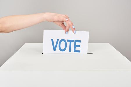 Vista parcial de la mujer poniendo la tarjeta con voto en la casilla aislada sobre fondo gris