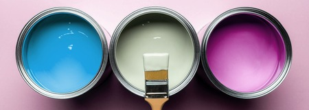 Panoramic shot of brush and cans with paints on pink surface