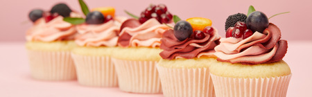 Panoramic shot of sweet cupcakes with berries and fruits on pink surface