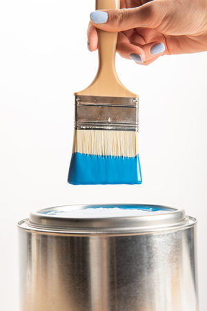 Partial view of woman holding brush with blue paint isolated on white background Standard-Bild - 122292349