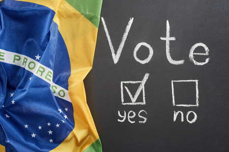 Top view of white vote word and check mark near yes word on black chalkboard near flag of Brazil 스톡 콘텐츠