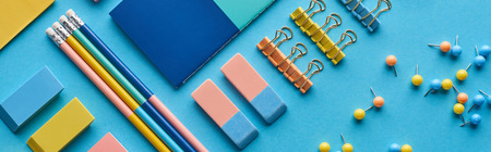 Panoramic shot of pencils, push pins and colorful stationery isolated on blue background