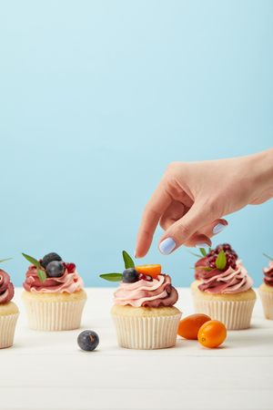 Partial view of woman with sweet cupcakes with berries 스톡 콘텐츠