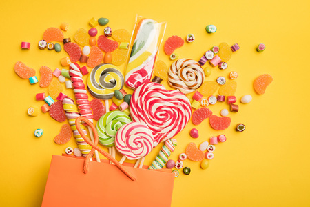 Top view of tasty multicolored sweets scattered from paper bag on bright yellow background