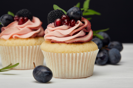 cupcakes with berries on white surface isolated on black