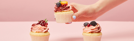 Panoramic shot of woman with sweet cupcakes on pink background