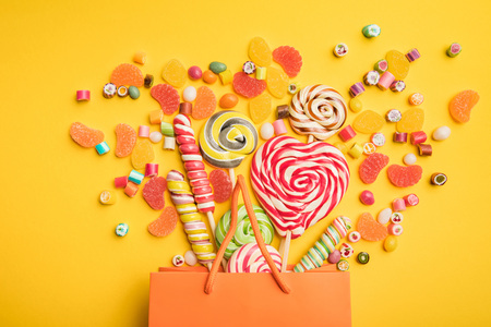 Top view of tasty multicolored candies scattered from paper bag on bright yellow background Stock Photo