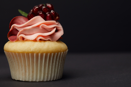 Cupcake with garnet on grey surface isolated on black background