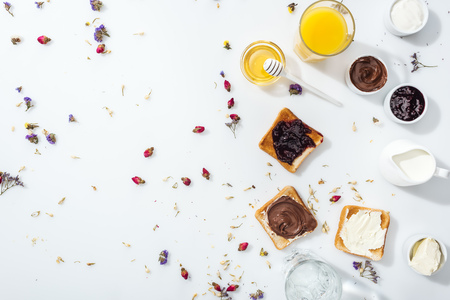 Top view of tasty toasts with jam, chocolate cream and cream cheese near glasses of orange juice and water on white background Banque d'images - 122292405