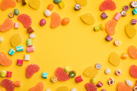 Top view of multicolored tasty caramel and fruit jelly candies scattered on yellow background with copy space Stock Photo