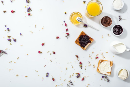 Top view of toasts with jam and cream cheese near glass of orange juice on white background Banque d'images - 122292469