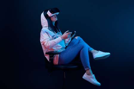 brunette woman sitting on chair and playing video game while wearing virtual reality headset on blue