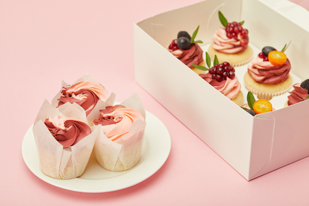 Box and plate with sweet cupcakes on pink surface