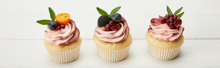 panoramic shot of cupcakes with fruits and berries on white surface