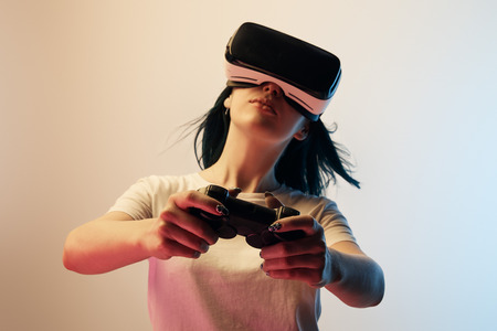 Selective focus of woman in white t-shirt wearing virtual reality headset and holding joystick on beige and blue background