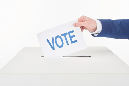 Cropped view of man putting card with vote lettering in box isolated on white background 스톡 콘텐츠