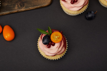 Top view of cupcakes with fruits and berries on black surface