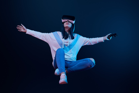 young woman in virtual reality headset levitating and holding joystick on blue 写真素材