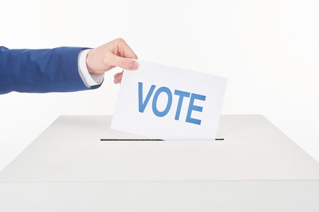 Partial view of man putting card with vote in box isolated on white background