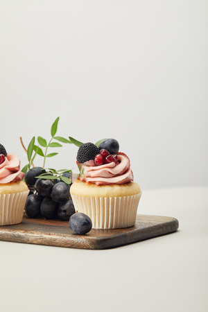 wooden cutting board with sweet cupcakes isolated on grey Banco de Imagens