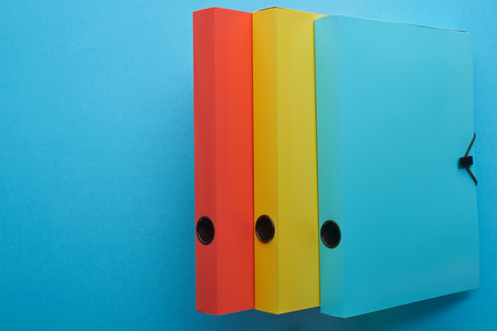 Top view of colorful paper binders isolated on blue with copy space