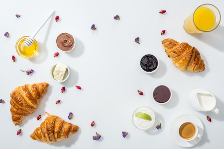 Top view of croissants near bowls with jam, orange juice and dried flowers on white background