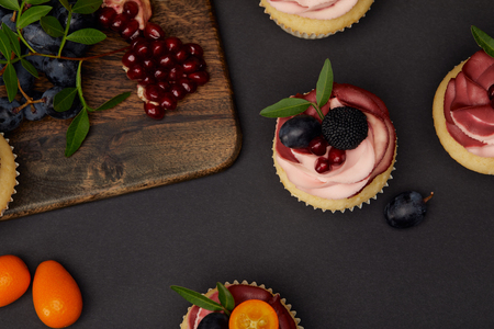 Top view of cupcakes, grapes, garnet and cutting board on black surface