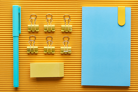 Top view of pen, notebook and colorful arranged office stationery supplies on yellow background