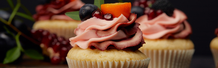 panoramic shot of cupcakes with cream, fruits and berries Banco de Imagens