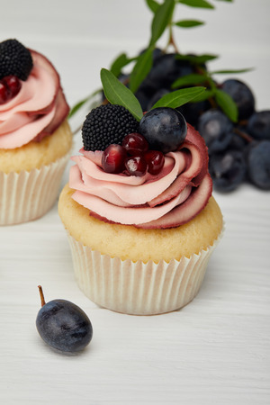 selective focus of cupcakes with cream and grapes on white surface