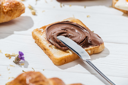 Enfoque selectivo de tostadas con crema de chocolate y cuchillo sobre fondo blanco.