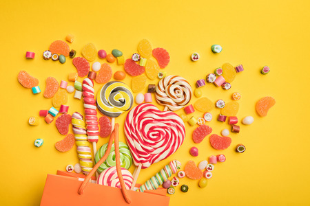 Top view of delicious multicolored candies scattered from paper bag on bright yellow background Stock Photo