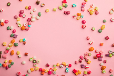 Top view of multicolored candies scattered on pink background with copy space