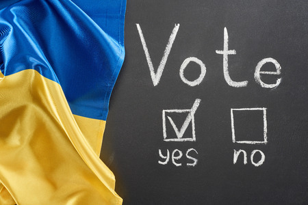 Top view of vote lettering and check mark near yes word on black chalkboard near Ukrainian flag Stock fotó