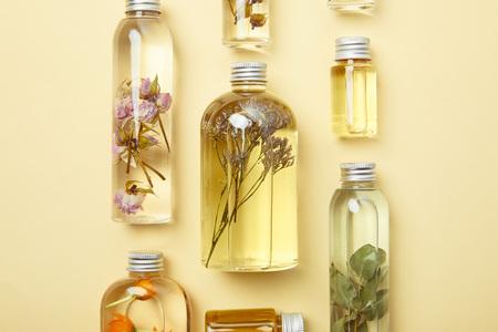 Draufsicht auf transparente Flaschen mit natürlichen Schönheitsprodukten und getrockneten Wildblumen auf gelbem Hintergrund