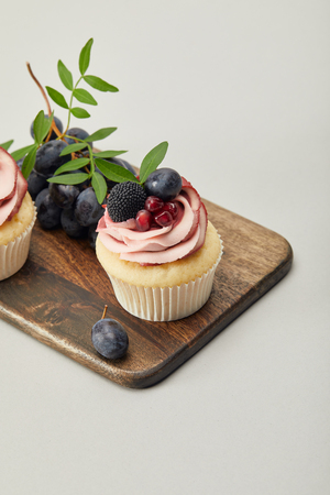 cupcakes with grapes on cutting board isolated on grey Banco de Imagens