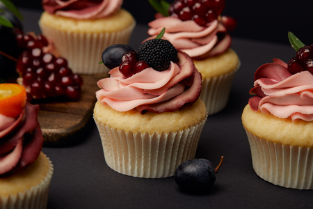 cupcakes with fruits and berries on black surface