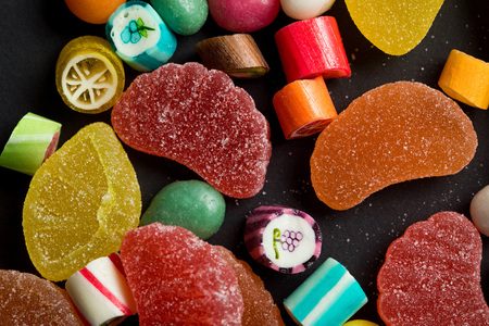 Close up view of caramel multicolored candies and sugary fruit jellies on black background
